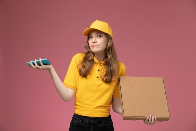 Вид спереди молодая женщина-курьер в желтой форме, держащая коробку для еды с телефоном на темно-розовом фоне, работник службы доставки униформы