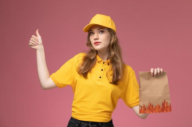 濃いピンクの机の上の食品配達パッケージを保持している黄色の制服を着た若い女性の宅配便の正面図制服配達サービスの女性労働者