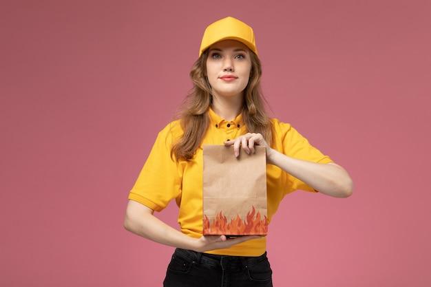 Вид спереди молодая женщина-курьер в желтой форме держит пакет с продуктами, доставляя его на розовом фоне, служба доставки униформы