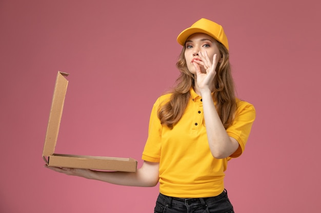 진한 분홍색 책상 유니폼 배달 서비스 여성 노동자에 그것을 여는 음식 패키지를 들고 노란색 제복을 입은 전면보기 젊은 여성 택배