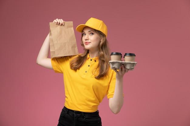 ピンクの背景の机の上の食品とコーヒーカップとパッケージを保持している黄色の制服を着た若い女性の宅配便の正面図仕事制服配達サービス労働者