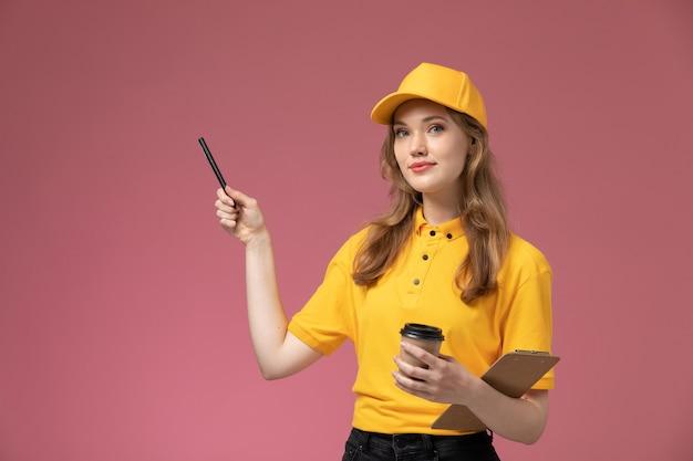 Вид спереди молодая женщина-курьер в желтой форме держит пластиковый коричневый блокнот с кофейной чашкой и ручку на розовом фоне.
