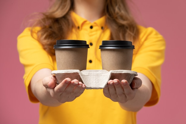濃いピンクの背景にプラスチック製の茶色のコーヒーカップを保持している黄色の制服を着た若い女性の宅配便の正面図仕事制服配達カラーサービスワーカー