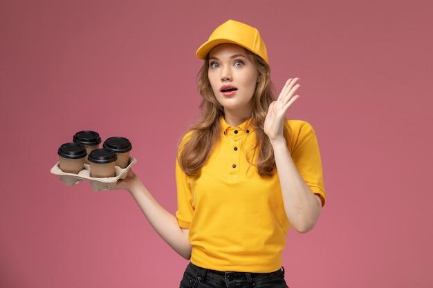 ピンクの暗い背景にプラスチック製の茶色のコーヒーカップを保持している黄色の制服を着た若い女性の宅配便の正面図