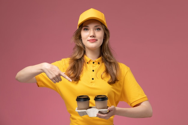 ピンクの背景の仕事の制服配達カラーサービスワーカーに彼女の顔に笑顔でプラスチック製の茶色のコーヒーカップを保持している黄色の制服を着た若い女性の宅配便の正面図