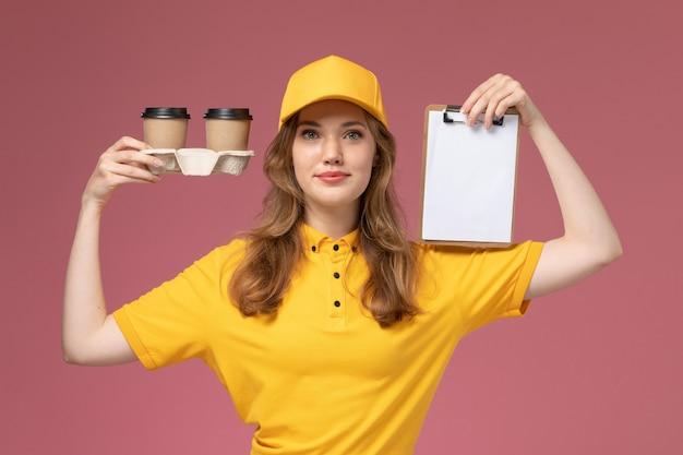Вид спереди молодая женщина-курьер в желтой форме, держащая пластиковые кофейные чашки и блокнот на темно-розовом столе, работник службы доставки униформы