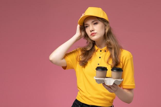 Вид спереди молодая женщина-курьер в желтой форме, держащая пластиковые кофейные чашки и думающая на темно-розовом фоне, работник службы доставки униформы