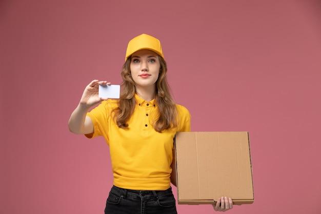 濃いピンクの机の上の白いカードと食品パッケージを保持している黄色の制服を着た若い女性の宅配便の正面図制服配達ジョブサービスワーカー