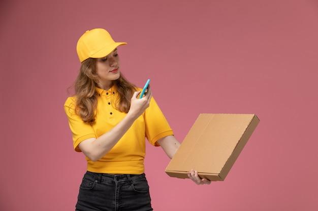 ピンクの背景の机の上の食品とパッケージの写真を撮る黄色の制服を着た若い女性の宅配便の正面図仕事制服配達サービスワーカー
