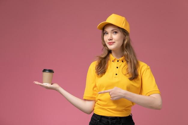 濃いピンクの背景に茶色のプラスチック製のコーヒーカップを保持している黄色の制服黄色のケープの正面図若い女性の宅配便制服配達ジョブサービスカラー