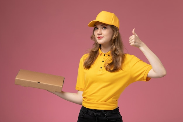 Вид спереди молодая женщина-курьер в желтой форме с желтым плащом, держащая коробку для доставки еды на темно-розовом фоне, цвет службы доставки униформы