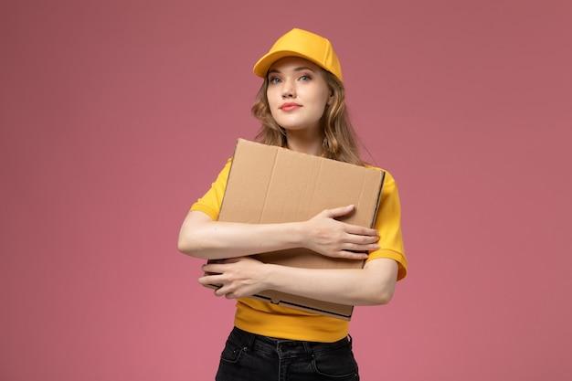 Вид спереди молодая женщина-курьер в желтой униформе с желтым плащом держит коробку для доставки еды на темно-розовом фоне.