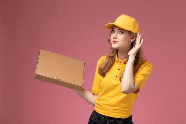 Вид спереди молодая женщина-курьер в желтой форме с желтым плащом, держащая коробку для доставки еды на темно-розовом фоне, служба доставки униформы
