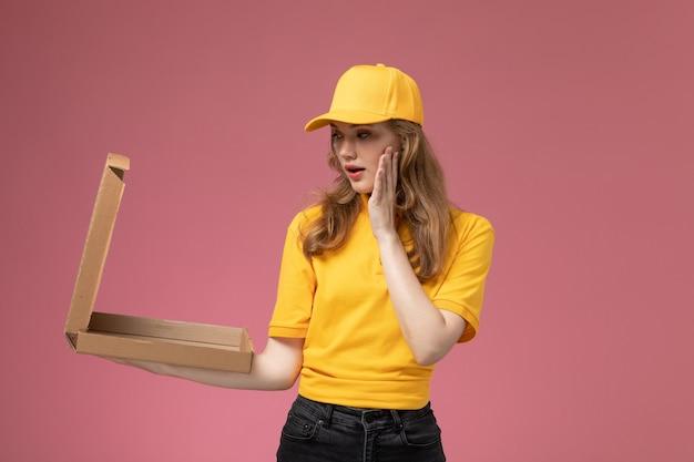 濃いピンクの背景にそれを開く食品配達ボックスを保持している黄色の制服黄色の岬の正面図若い女性の宅配便制服配達ジョブサービスの色