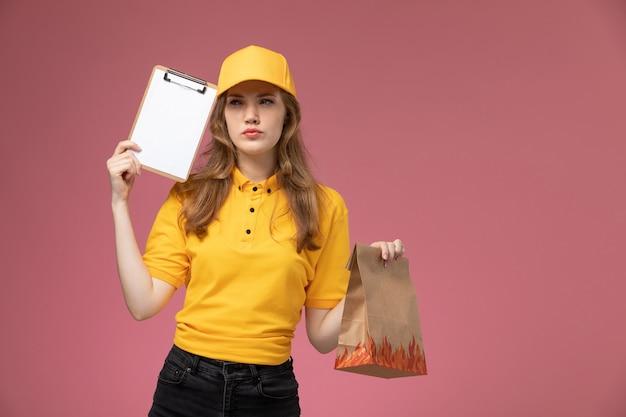 濃いピンクの床に食品配達パッケージのメモ帳を保持している黄色の制服黄色のケープの正面図若い女性の宅配便制服配達サービスの女性労働者