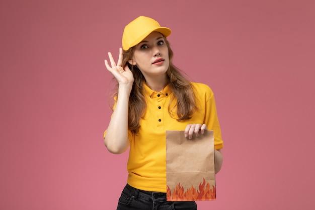 Вид спереди молодая женщина-курьер в желтой форме с желтым плащом, держащая посылку с доставкой еды на темно-розовом фоне, цвет службы доставки униформы