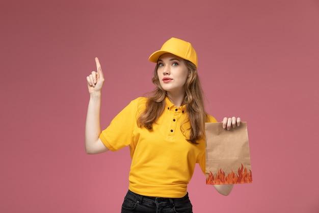 濃いピンクの背景に食品配達パッケージを保持している黄色の制服黄色の岬の正面図若い女性の宅配便制服配達サービス女性労働者