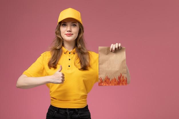 Вид спереди молодая женщина-курьер в желтой униформе желтого плаща с улыбкой держит посылку с доставкой еды на темно-розовом фоне.