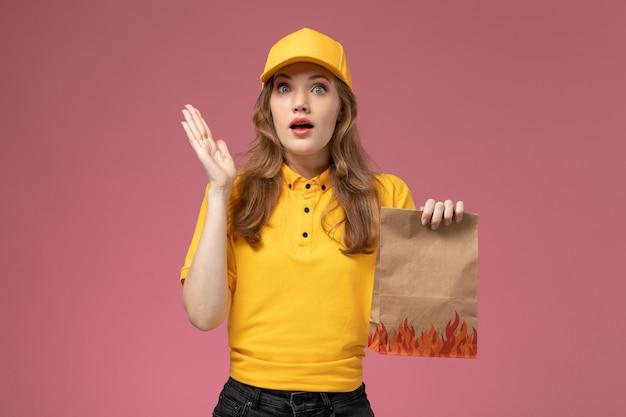 Вид спереди молодая женщина-курьер в желтой униформе, желтой накидке, держащей пакет с продуктами на темно-розовом фоне, работница службы доставки униформы