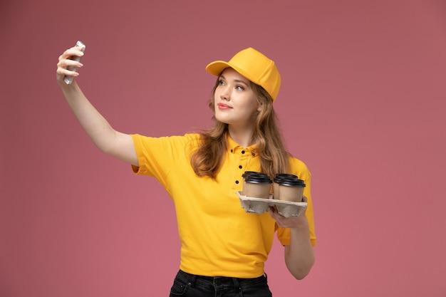 Вид спереди молодая женщина-курьер в желтой униформе с желтым плащом, делающая селфи с кофе на темно-розовом фоне, цвет службы доставки униформы