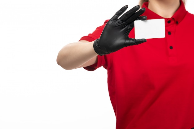 A front view young female courier in red shirt black leather gloves holding white card on the white background uniform service delivering