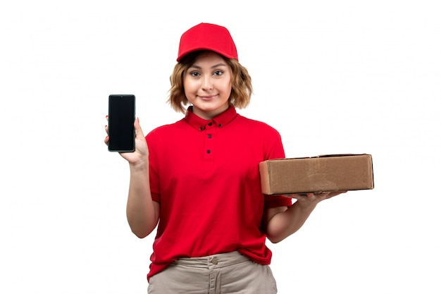 A front view young female courier in red shirt red cap holding delivery package and smartphone smiling
