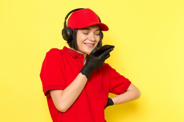 A front view young female courier in red uniform black gloves and red cap in earphones sending voice message