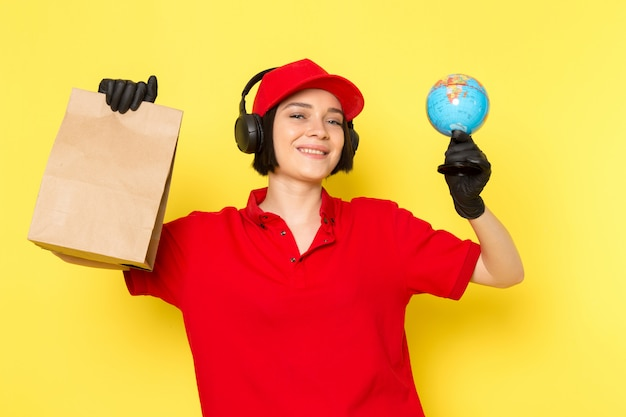 A front view young female courier in red uniform black gloves and red cap holding food box and little globe