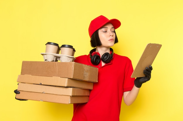 A front view young female courier in red uniform black gloves and red cap holding food boxes and coffee cups