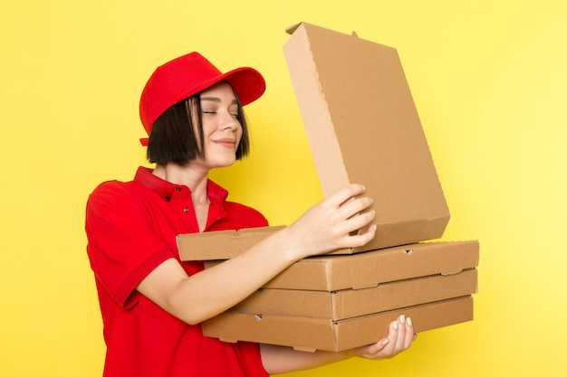 A front view young female courier in red uniform black gloves and red cap holding food boxes