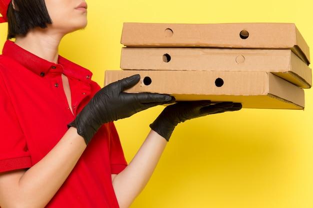 Un corriere femminile giovane di vista frontale in guanti neri uniformi rossi e spiritello malevolo che tengono le scatole di alimento