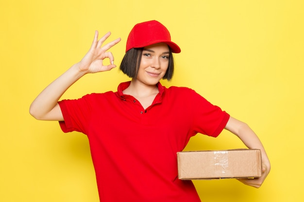 A front view young female courier in red uniform black gloves and red cap holding food package showing alright sign
