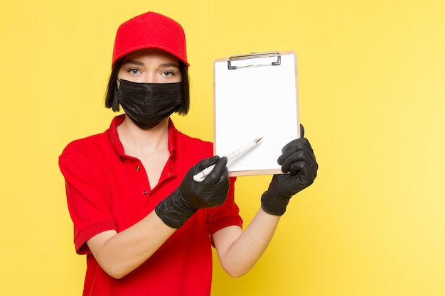A front view young female courier in red uniform black gloves and red cap holding notepad