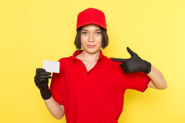 Una vista frontale giovane corriere femminile in uniforme rossa guanti neri e berretto rosso