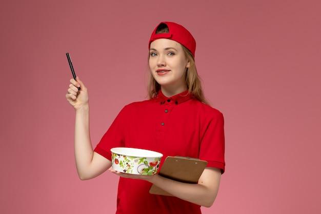 Giovane corriere femminile di vista frontale in uniforme rossa e ciotola di consegna della tenuta del capo e blocco note con la parete rosa della penna