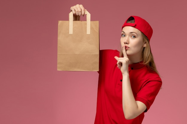 Front view young female courier in red uniform and cape holding delivery food package on light-pink wall