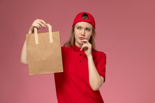 Giovane corriere femminile di vista frontale in uniforme rossa e mantello che tiene il pacchetto di cibo di consegna e pensa sulla parete rosa