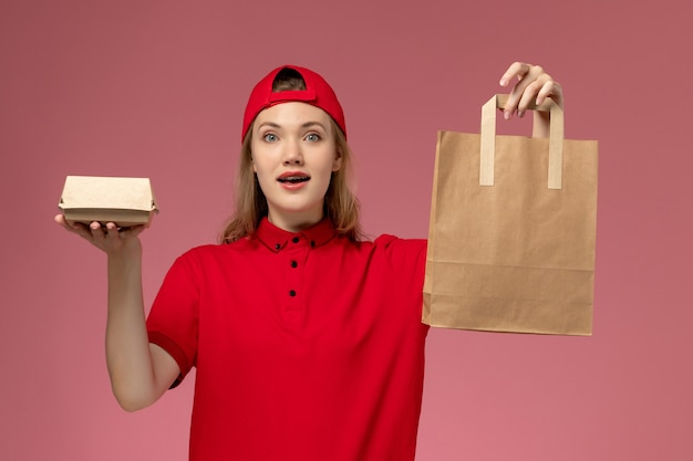 Front view young female courier in red uniform and cape holding delivery food packages on the pink wall