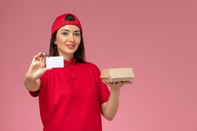 Front view young female courier in red uniform cape with little delivery food package and card on her hands on light-pink desk service delivery employee