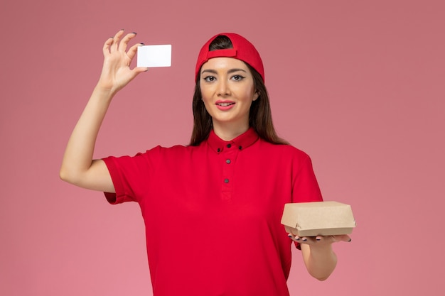 Front view young female courier in red uniform cape with little delivery food package and card on her hands on light-pink wall
