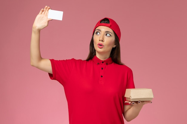 Front view young female courier in red uniform cape with little delivery food package and card on her hands on pink wall