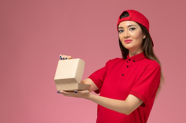 Front view young female courier in red uniform and cape with little delivery food package on her hands on light pink wall