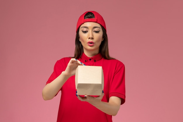 Front view young female courier in red uniform and cape with little delivery food package on her hands opening it on light pink wall