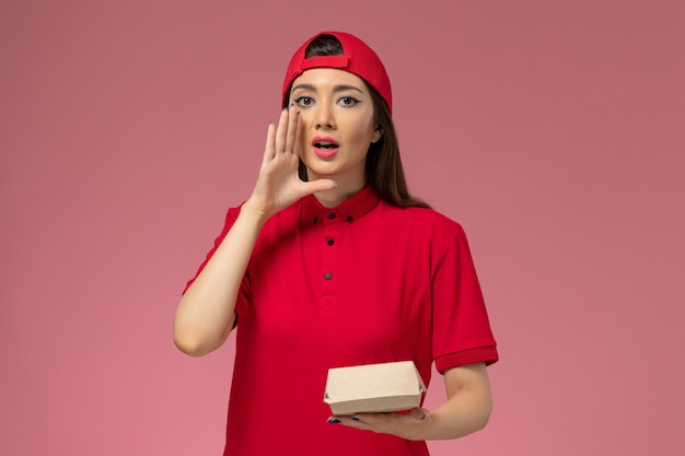 Front view young female courier in red uniform and cape with little delivery food package on her hands on pink desk uniform delivery service