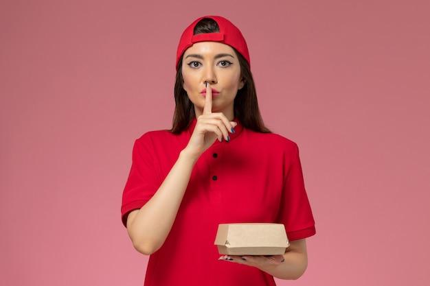 Corriere femminile giovane vista frontale in uniforme rossa e mantello con poco pacchetto di cibo di consegna sulle sue mani sul muro rosa
