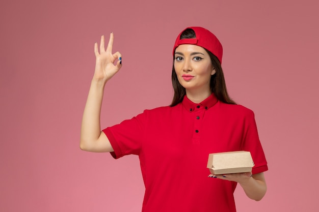 Front view young female courier in red uniform and cape with little delivery food package on her hands on pink wall