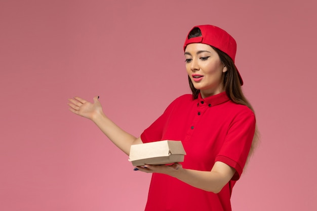 Front view young female courier in red uniform and cape with little delivery food package on her hands on the pink wall