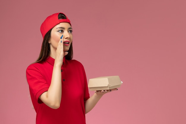Front view young female courier in red uniform and cape with little delivery food package on her hands and whispering on pink wall