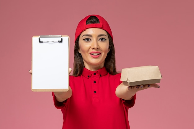 Front view young female courier in red uniform cape with little delivery food package and notepad on her hands on light-pink wall