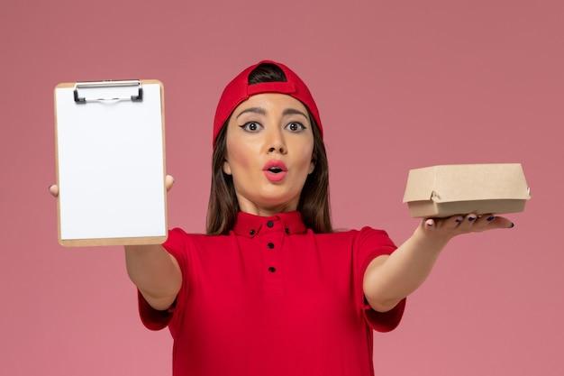 Giovane corriere femminile di vista frontale in mantello rosso uniforme con piccolo pacchetto di cibo di consegna e blocco note sulle sue mani sulla parete rosa chiaro